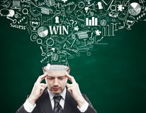 Thoughtful businessman with business sketch. Thoughtful young businessman with business sketch coming out of his head on chalkboard background. Brainstorming Stock Photos