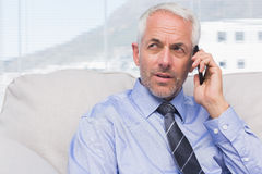 Thoughtful businessman calling on smartphone Stock Photo