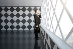 Thoughtful businessman in chessboard interior Stock Photography