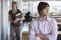 Thoughtful Businessman and colleague in office. Thoughtful young businessman with blurred female colleague in the background at office Royalty Free Stock Images