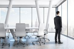 Thoughtful businessman in conference room. Thoughtful young businessmen standing in modern conference room interior with panoramic city view. Career, job and stock photos