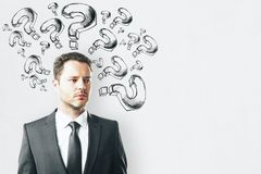 Ask and confusion concept. Thoughtful businessman with drawn question marks on concrete background. Ask and confusion concept stock photography