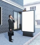 Businessman with empty ad stand. Thoughtful businessman and empty blank ad stand on the street next to black brick building. Mock up, 3D Rendering Stock Photography