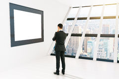 Thoughtful businessman frame. Thoughtful businessman looking at blank picture frame in white room with windows and city view. Mock up, 3D Rendering Stock Photos