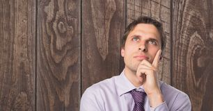 Thoughtful businessman with hand on chin against wooden wall royalty free stock photo