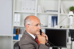 Thoughtful Businessman With Hand On Chin Using Landline Phone Stock Photos