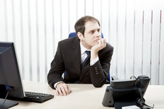 Thoughtful businessman in his office. Sitting at his desk resting his chin on his hand as he stares into the distance while contemplating difficult decisions Royalty Free Stock Image