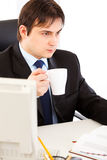 Thoughtful businessman holding cup of tea in hand Stock Image