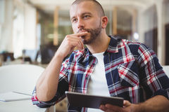 Thoughtful businessman holding digital tablet Royalty Free Stock Photos
