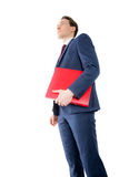 Thoughtful businessman holding red folder Stock Photo