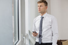 Thoughtful businessman holding smart phone while looking through window at home Royalty Free Stock Photo