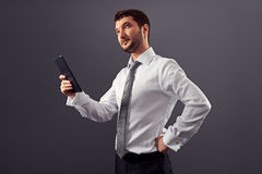 Businessman holding tablet pc and looking up Royalty Free Stock Images