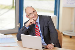 Thoughtful Businessman With Laptop At Desk Stock Images
