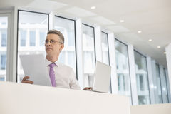 Thoughtful businessman with laptop and documents at railing Stock Images