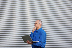 Thoughtful Businessman With Laptop While Looking Away Royalty Free Stock Images