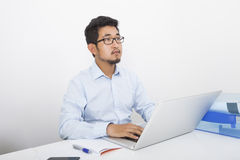 Thoughtful businessman with laptop sitting at desk in office Stock Images
