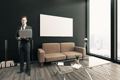 Thoughtful businessman with laptop. Thoughtful young businessman using laptop in modern interior with coffee table, sofa, blank poster on wall and city view Stock Photos
