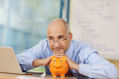 Thoughtful Businessman Leaning On Piggybank At Desk Stock Photo