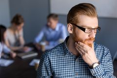 Thoughtful businessman looking away holding hand on chin plannin stock photography