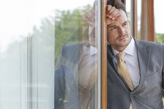 Thoughtful businessman looking away while leaning on glass door Royalty Free Stock Photography