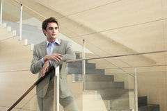 Thoughtful Businessman Looking Away While Leaning On Glass Raili Royalty Free Stock Images