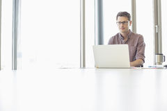 Thoughtful businessman looking away while using laptop at desk in creative office Royalty Free Stock Images
