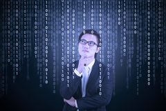 Thoughtful businessman looking at binary code Stock Images