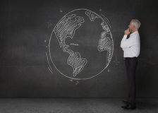 Thoughtful businessman looking at an earth drawn with a chalk Royalty Free Stock Photo