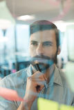 Thoughtful businessman looking at plans written on glass Royalty Free Stock Photography