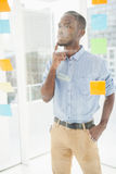 Thoughtful businessman looking at sticky notes on window Stock Photo