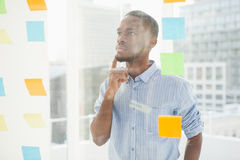 Thoughtful businessman looking at sticky notes on window Stock Image