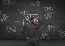 Thoughtful businessman looking at Tic-tac-toe game Stock Photography