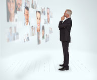 Thoughtful businessman looking at a wall covered by profile pictures. On white background Stock Photos