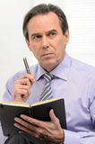 Thoughtful businessman. Mature businessman sitting with a note p Stock Images