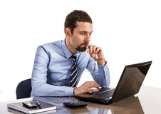 Thoughtful businessman at office desk looking on laptop isolated on white background Royalty Free Stock Photography