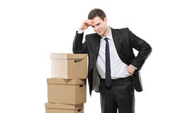 Thoughtful businessman with paper boxes Stock Photo
