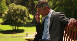 Thoughtful businessman in the park stock footage