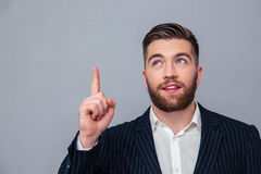 Thoughtful businessman pointing finger up Stock Photos
