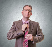 Thoughtful businessman putting his tie on white background Royalty Free Stock Photography