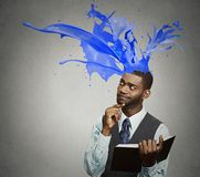 Thoughtful businessman reading book colorful splashes coming out of head Royalty Free Stock Images