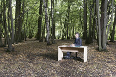 Thoughtful Businessman Sitting At Desk In Forest Royalty Free Stock Photography