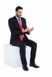 Thoughtful businessman sitting holding something Stock Photo