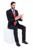 Thoughtful businessman sitting reading book Stock Photography