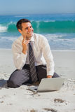 Thoughtful businessman sitting on the sand with his laptop Stock Images