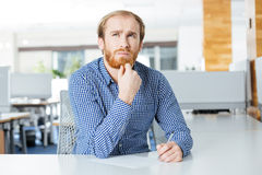 Thoughtful businessman sitting at the table in office and writing Royalty Free Stock Image