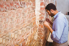 Thoughtful businessman standing against brick wall Stock Photo