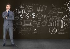 Thoughtful businessman standing against business symbols on blackboard royalty free stock photo