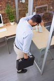 Thoughtful businessman standing against glass wall Stock Photography
