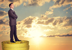 Thoughtful businessman standing on coins stack Stock Images
