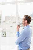 Thoughtful businessman standing and holding his glasses Royalty Free Stock Photos